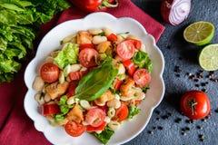 与油煎的鱼、红辣椒、葱和香葱的白豆沙拉 免版税库存图片