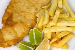 与油煎的鱼大服务的盐味的炸薯条用柠檬 免版税库存照片