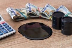 与油的黑桶在与计算器的美元钞票说谎在书桌上 免版税库存照片