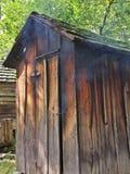 与泄漏的烟的土气老肉吸烟房 库存图片