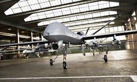 与法令的军事寄生虫UAV航空器` s在位置在等候罢工使命的飞机棚 免版税库存图片