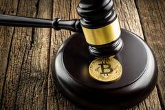 与法官木锤子法律的金黄bitcoin硬币判断背景 图库摄影