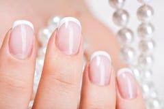 与法式修剪和珍珠的美丽的妇女的钉子 免版税库存照片