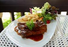与法语油煎的和莴苣沙拉的烤肋骨牛排服务 库存图片