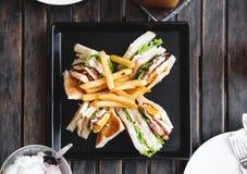 与法语的四个切片三明治在黑角规盘油煎了,在木桌上 免版税库存图片