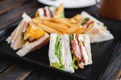 与法语的四个切片三明治在黑角规盘油煎了,在木桌上 免版税库存照片