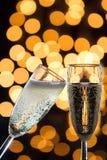 与泡影和bokeh光的两块香槟玻璃在后面 免版税库存图片