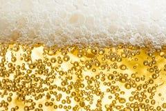 与泡影特写镜头的金冰冷的啤酒泡沫 库存照片