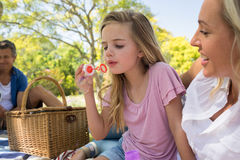 与泡影鞭子的母亲和女儿吹的泡影在野餐在公园 免版税库存照片