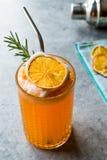 与泡沫、罗斯玛丽和金属秸杆的干橙色鸡尾酒 库存图片