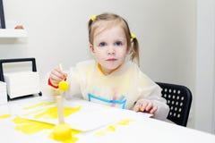 与泡沫刷子的逗人喜爱的可爱的女孩绘画在家 免版税库存照片