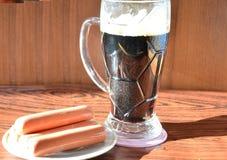 与泡沫和快餐快餐的黑啤酒 库存照片