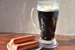 与泡沫和快餐快餐的黑啤酒 免版税库存照片