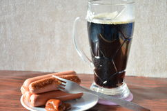 与泡沫和快餐快餐的黑啤酒 图库摄影