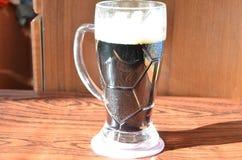 与泡沫和快餐的黑啤酒 库存图片