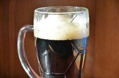 与泡沫和快餐的黑啤酒 免版税图库摄影