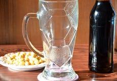 与泡沫和瓶,快餐的黑啤酒 库存照片