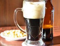与泡沫和瓶,快餐的黑啤酒 库存图片