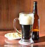 与泡沫和瓶,快餐的黑啤酒 免版税库存照片