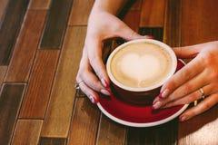 与泡沫心脏的咖啡热奶咖啡在妇女手上 免版税库存图片