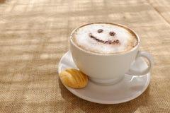 与泡沫或巧克力微笑的受欢迎的愉快的面孔的咖啡热奶咖啡 库存图片