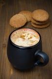 与泡沫的无奶咖啡和麦甜饼在背景中 库存照片
