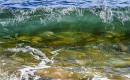 与泡沫的沿海透明海/海洋碰撞的波浪在它的上面 库存照片