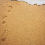 与泡沫的海波浪和在沙子的人的脚印 免版税库存照片