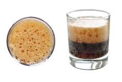 与泡沫的碳酸化合的冷的饮料在白色背景的玻璃杯 免版税库存照片
