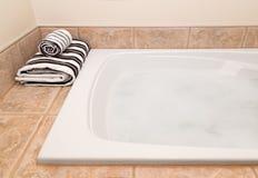 与泡沫的被折叠的镶边毛巾和浴 库存照片