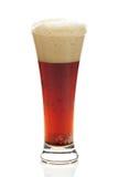 与泡沫的黑啤酒在一块高玻璃 图库摄影