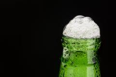 与泡沫的绿色啤酒瓶脖子在黑色 免版税库存图片