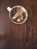 与泡沫艺术和巧克力漩涡的一杯被享用的上等咖啡,在木背景 库存照片