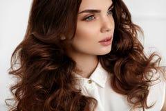 与波浪卷曲发型的美好的女孩模型 布朗头发颜色 库存照片
