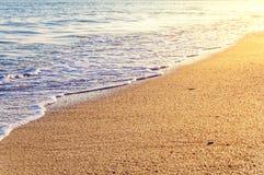 与波浪和灼烧的太阳的热带沙子海滩 库存图片