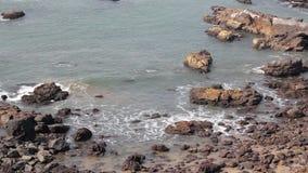 与波浪和石头的岩石沿海在反对蓝色海洋,鸟瞰图的水中 股票视频