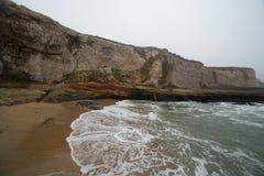 与波浪明亮的镶边沿海岩石的海洋峭壁 图库摄影