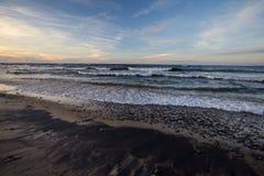 与波浪的日落海滩在苏必利尔湖在密执安 免版税库存照片