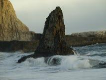 与波浪的沿海岩石日落 免版税库存照片