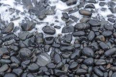 与波浪的黑小卵石在海海滩 免版税库存照片