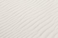 与波浪背景纹理的白色沙子 免版税库存照片