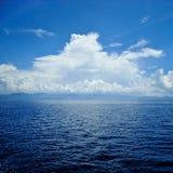 与波纹和天空的清楚的蓝色海表面与在它的云彩 免版税库存照片