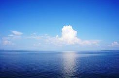 与波纹和天空的清楚的蓝色海表面与蓬松云彩 库存图片