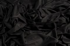 与波纹和纹理的明亮的黑织品与坚硬光和黑暗的光 免版税库存照片