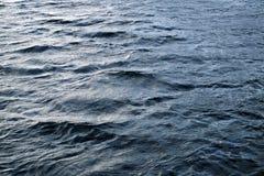 与波纹和轻的强光的不安定的水表面 图库摄影