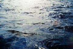 与波纹和阳光反射的水表面 免版税库存照片