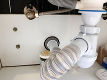 与波纹状的管子和虹吸管的污水在卫生间里 免版税库存照片