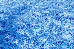 与波纹的明亮的蓝色水池水背景纹理 免版税库存照片