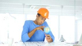 与注意的美国黑人的建筑工程师读书世界地球 免版税库存图片