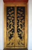与泰国式被镀金的黑亮漆的古老门 库存照片